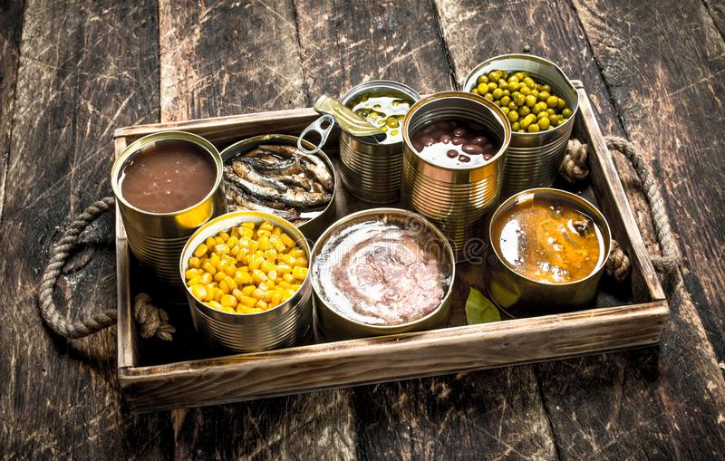Various canned fruits, vegetables, fish and meat in tin cans on old tray. On a wooden background royalty free stock photography