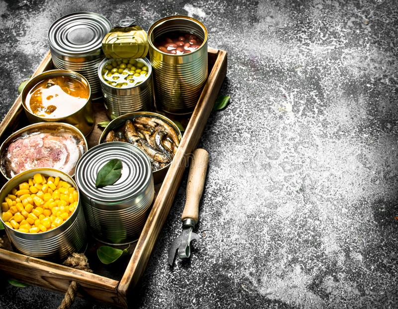 Various canned products in tin cans on a wooden tray. On a rustic background stock images