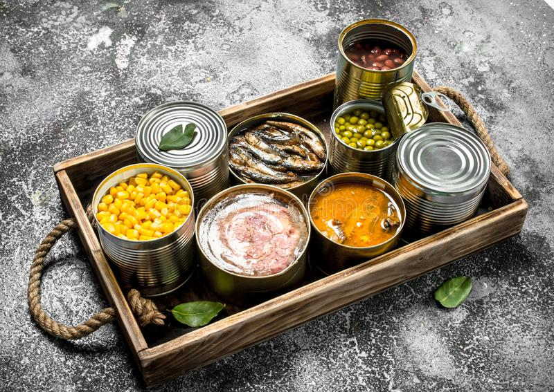 Various canned products in tin cans on a wooden tray. On a rustic background stock photography