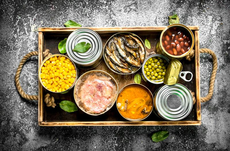 Various canned products in tin cans on a wooden tray. On a rustic background stock photos