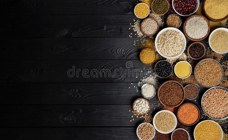 Cereals, grains, seeds and groats black wooden background stock images