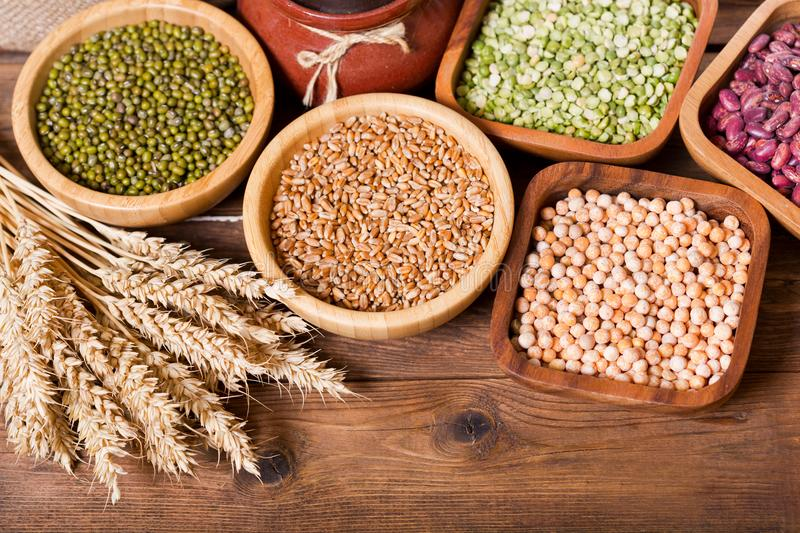 Various cereals, seeds, beans and grains on wooden table royalty free stock photos