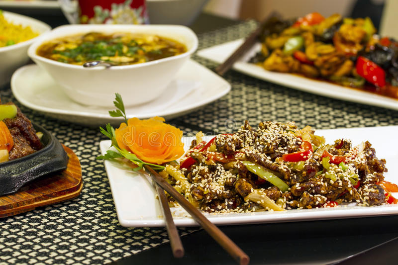 Various chinese food. Dishes on table, including soup and beef specialty. Selective focus stock images