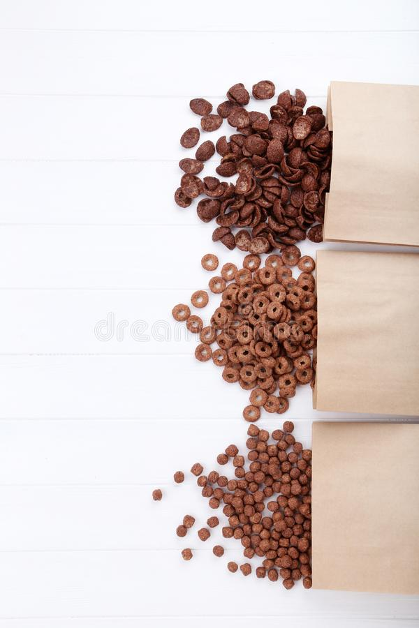 Chocolate corn flakes with paper bags. Various chocolate corn flakes with paper bags on white wooden table royalty free stock image