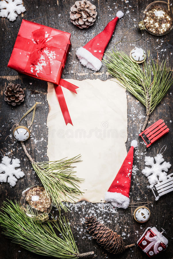 Various Christmas decorations around blank sheet of paper, gift box, Santa hat and snowflakes on rustic wooden background, top vie stock image