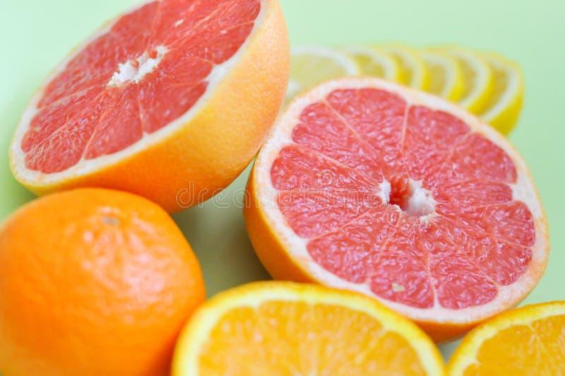 Various citrus fruits: grapefruit, orange, lemon and Mandarin on a green background stock photography