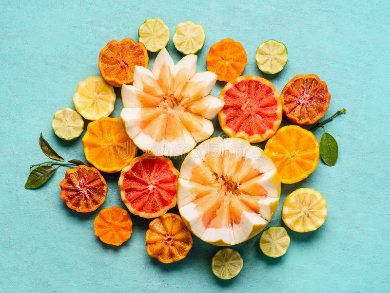 Various citrus fruits on light blue background, top view. Composing with half of orange fruits, lemon, grapefruit, mandarin, lime stock photos