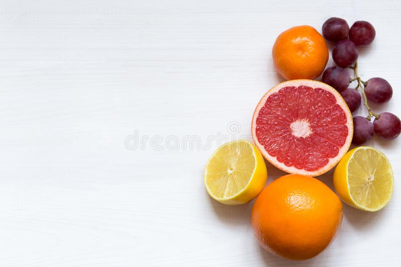 Various citrus fruits on white background, top view, copy space royalty free stock images