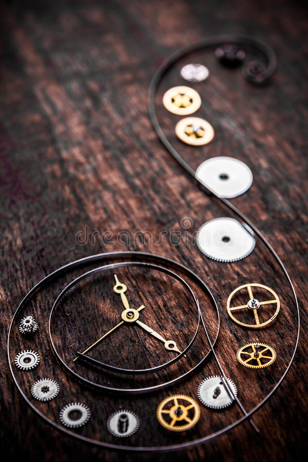 Various clock parts. (cogs, hands, springs) laid on a rustic/antique wood background, viewed from above royalty free stock photo