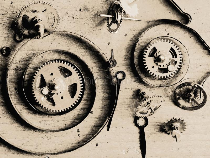 Clock parts wood. Various clock parts laid on a rustic wood background, viewed from above royalty free stock photography