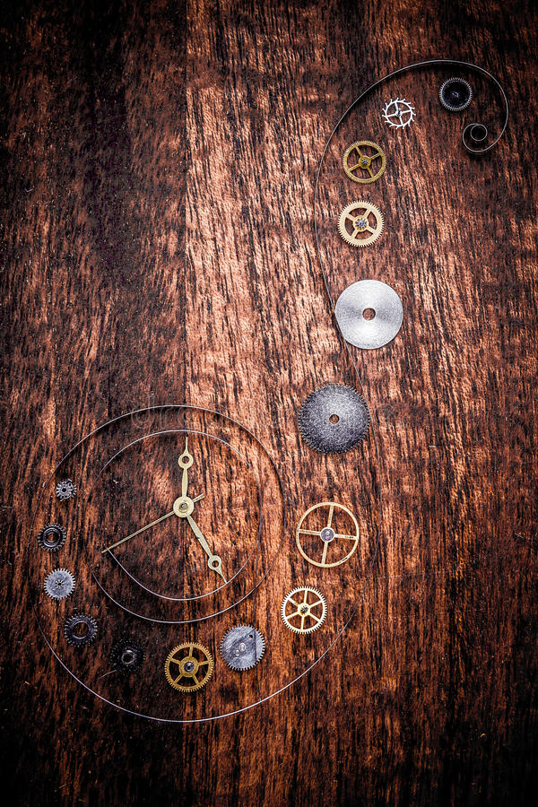 Various clock parts on a rustic wood. Various clock parts (cogs, hands, springs) laid on a rustic/antique wood background, viewed from above royalty free stock photos