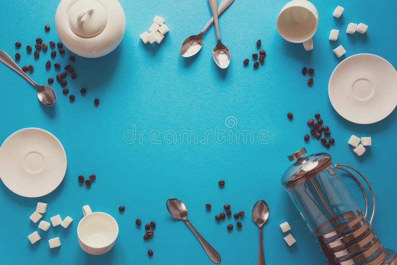 Various coffee making accessories: French coffee press, cups, saucers, coffee beans, spoons and sugar on blue paper background. Good morning concept. Space for stock photo