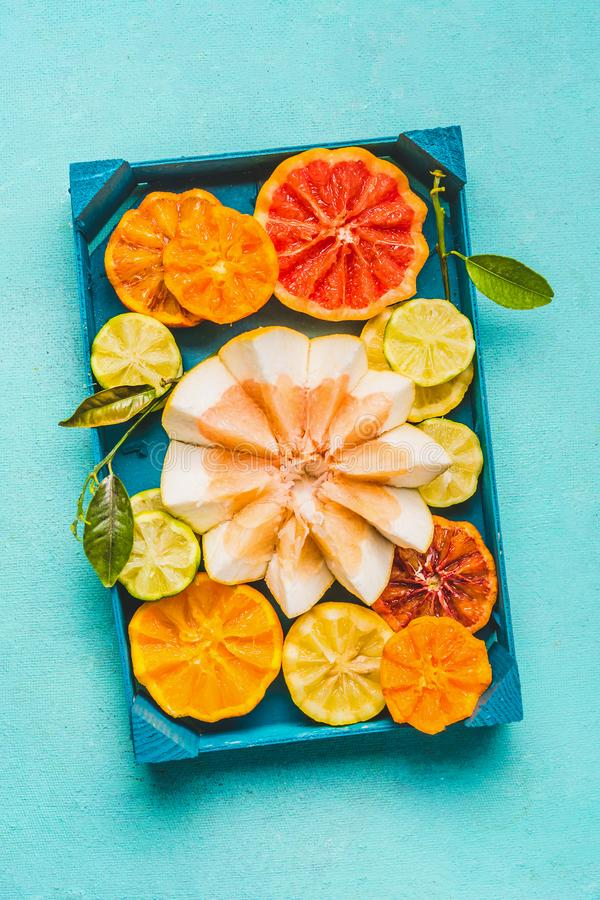 Various colorful citrus fruits halves with green leaves in wooden tray on light blue background, top view. Source of vitamin C. Healthy food ad lifestyle stock images