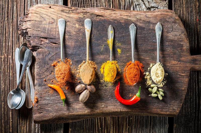 Various colorful condiments on spoons. On old wooden table royalty free stock images