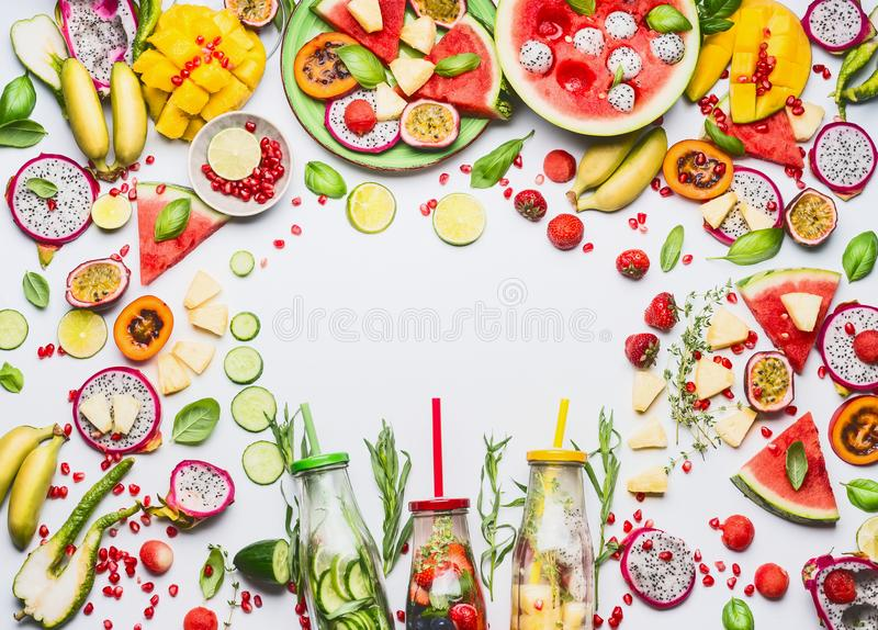 Various colorful sliced fruits, berries, vegetables ,herbs, infused water in bottles on white background, top view, frame royalty free stock image