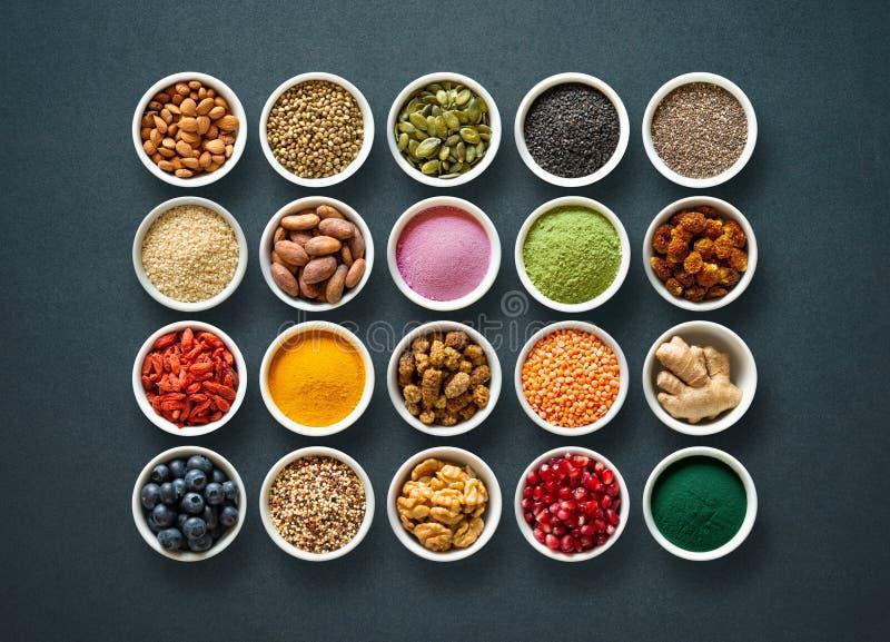 Various colorful superfoods in bowls on dark background. Various colorful superfoods as acai powder, turmeric, matcha green tea, spirulina, quinoa, pumpkin seeds stock photos