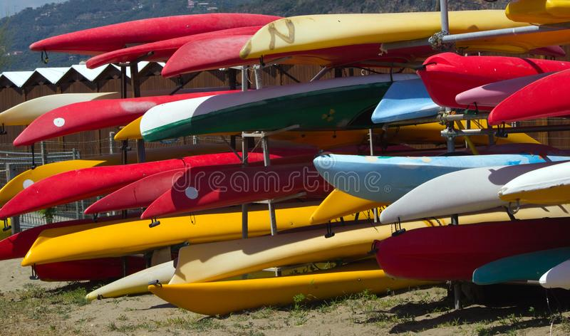 Colourful canoes along a sea front. Various coloured canoes ready to be hired on an Italian beach stock image