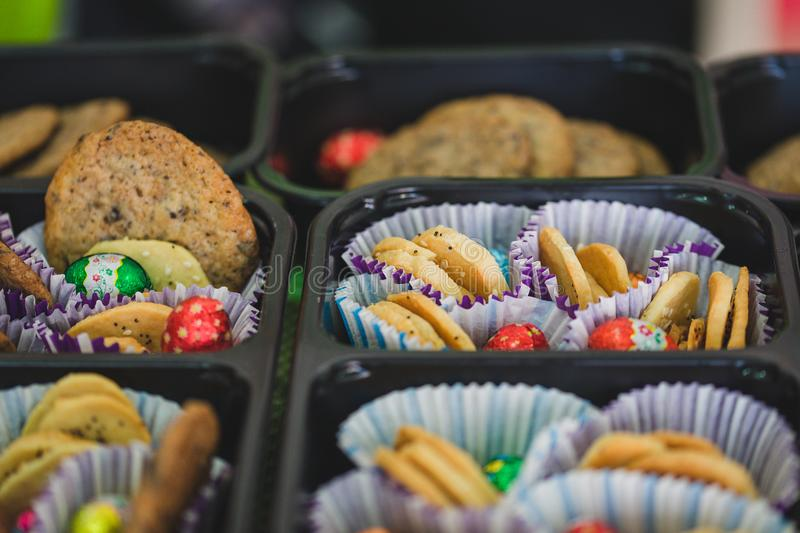 Various colourful biscuits in paper and trays, crunchy dessert for children stock photo