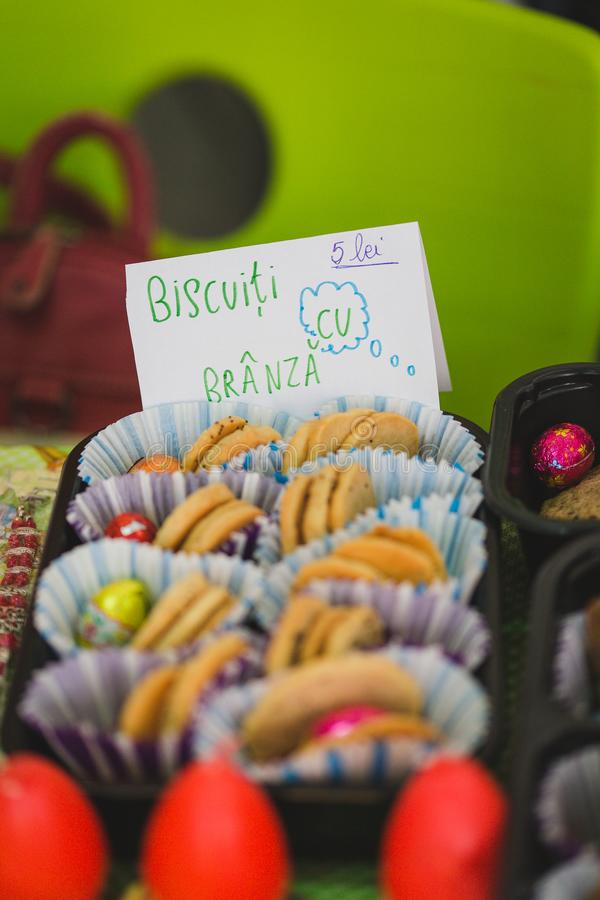Various colourful biscuits in paper and trays, handwritten tag by kids, Romanian. School market stock photography