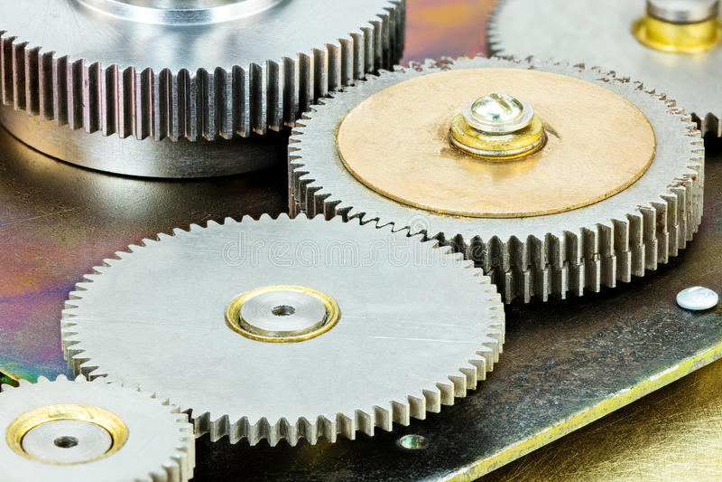 Various connecting metallic gearwheels of industrial mechanism stock photos