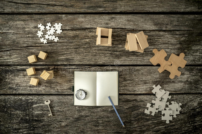 Various cubes, pegs, puzzles and a key lying on wooden desk around an open notepad stock photography