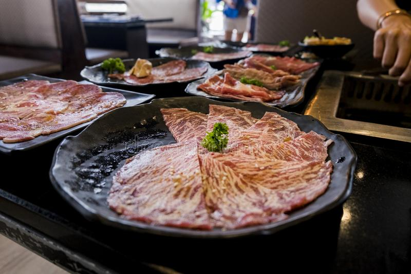 Various cuts of raw meat shot from above on a cast iron grill stock images