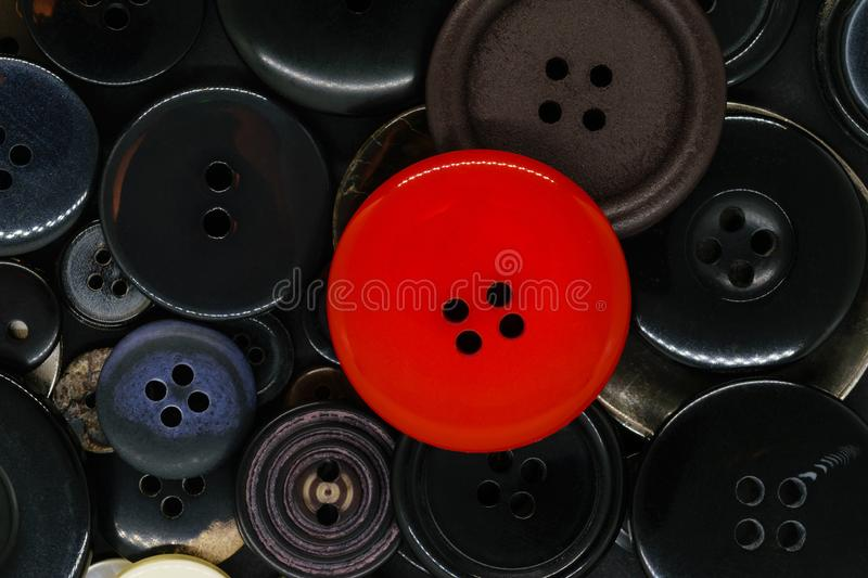 Various dark clothes buttons background with one red button royalty free stock photos