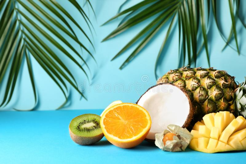 Various delicious exotic fruits with tropical leaves on color background royalty free stock photo