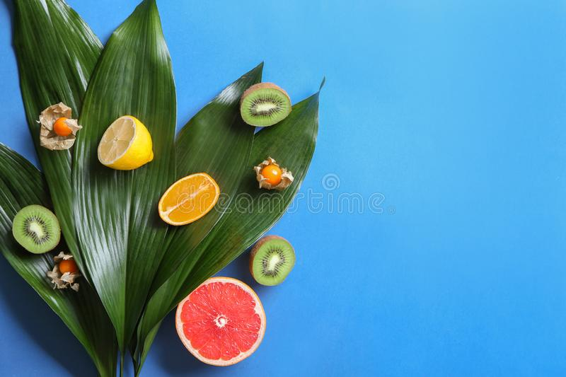 Various delicious exotic fruits with tropical leaves on color background royalty free stock photography