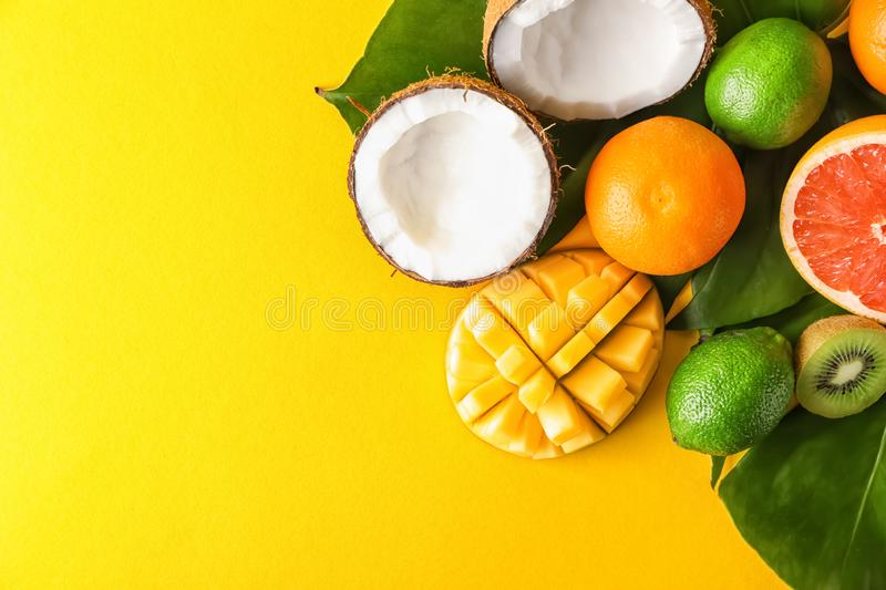 Various delicious exotic fruits with tropical leaves on color background stock images