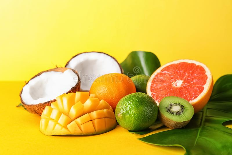 Various delicious exotic fruits with tropical leaves on color background royalty free stock images