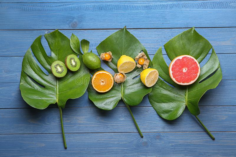 Various delicious exotic fruits with tropical leaves on color wooden background stock photography