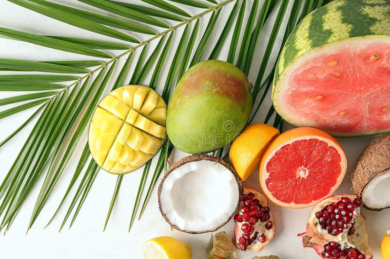 Various delicious fruits with tropical leaf on light table royalty free stock photo