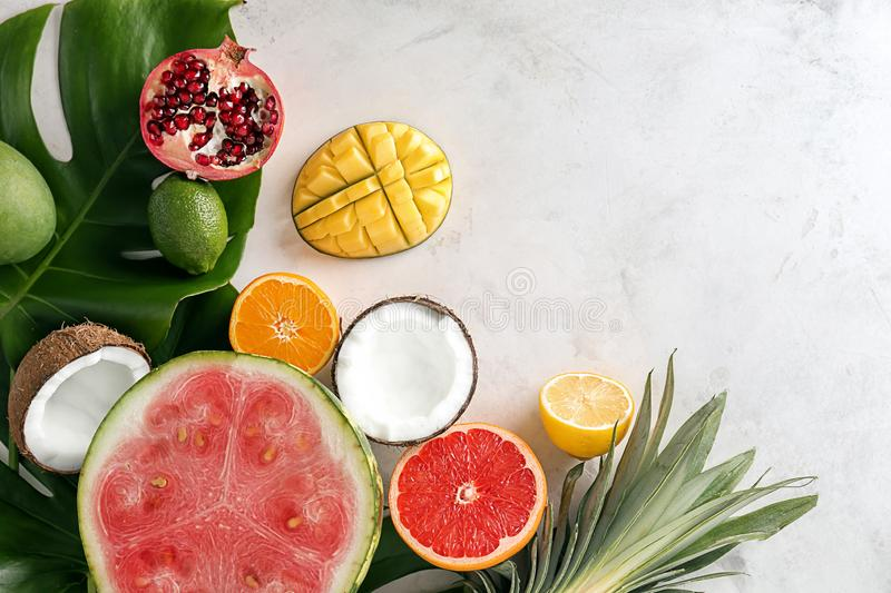 Various delicious fruits with tropical leaves on light table royalty free stock images