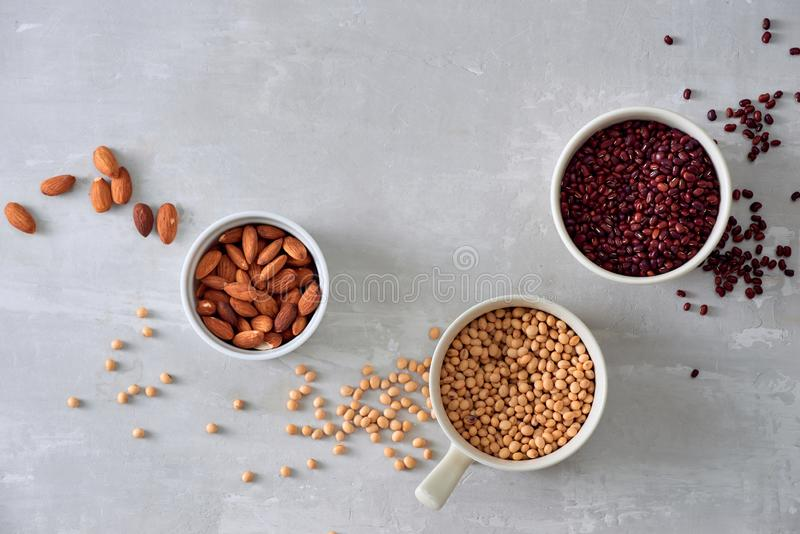 Various dried beans with kitchen utensils on gray table, top view stock photography