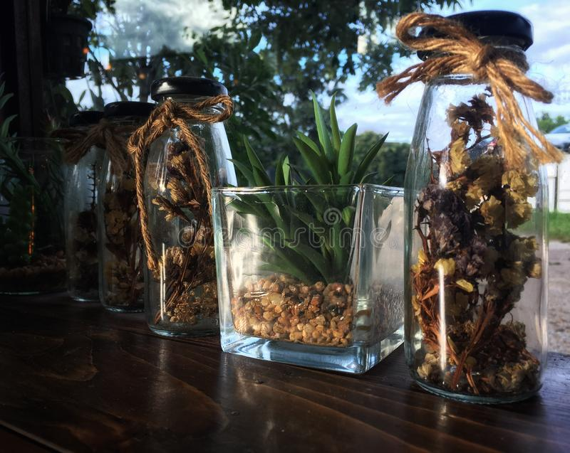 Various dried flowers and artificial flowers in the close bottle on wooden table stock images