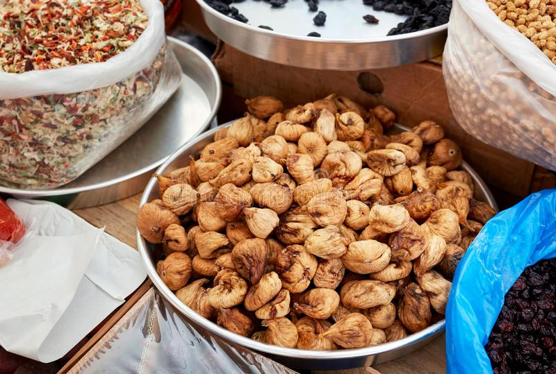 Various dried fruits in an authentic bazaar. Dry figs in a round metal pan in an authentic Turkish bazaar stock photos