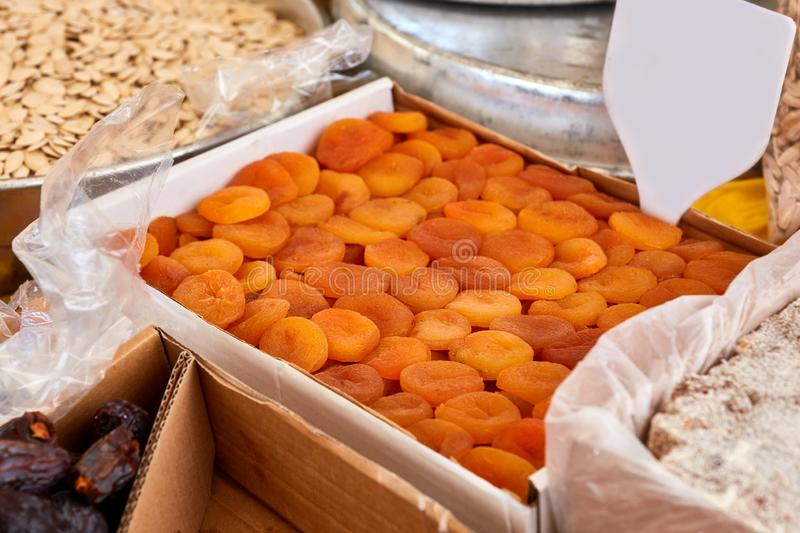 Various dried fruits in an authentic bazaar. Pile of dried apricots with empty price tag in an authentic bazaar royalty free stock images