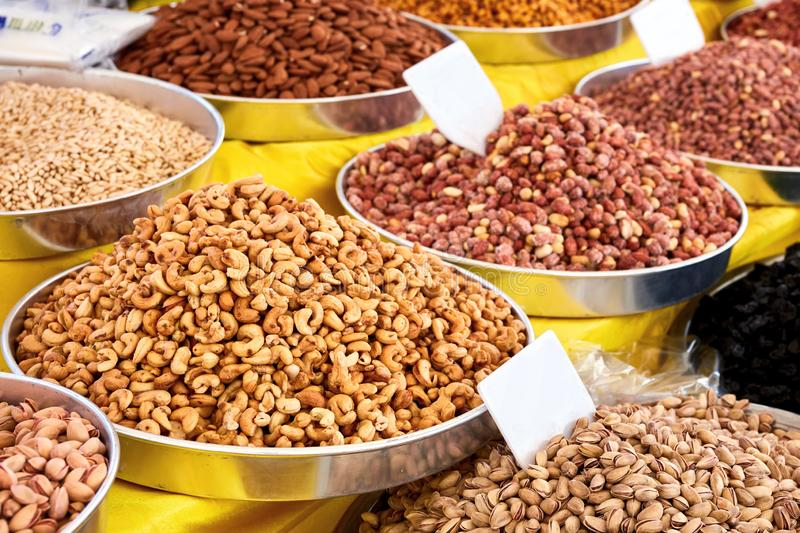 Various dried fruits in an authentic bazaar. Pile of cashew nut, pistachio, and roasted peanut in round metal trays in an authentic Turkish bazaar royalty free stock photo
