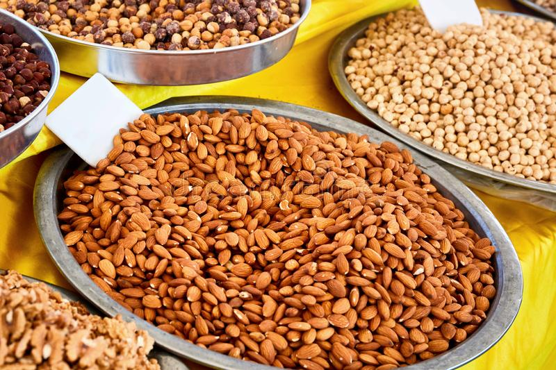 Various dried fruits in an authentic bazaar. Pile of delicious fresh almond and nut in round metal trays in an authentic bazaar stock photos