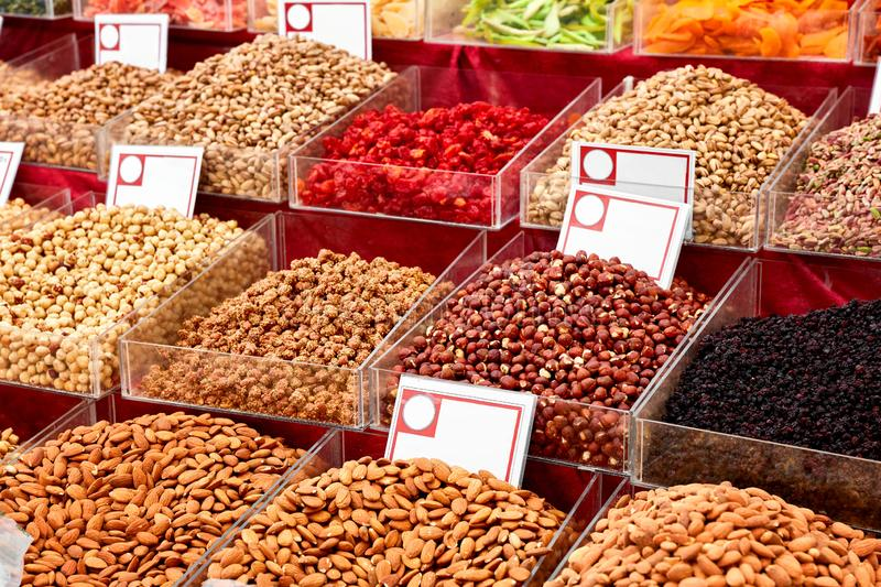 Various dried fruits in an authentic bazaar. Pile of dried nut, almond, pistachio, red and black currant , and peanut with sesame on the counter of an authentic royalty free stock photo