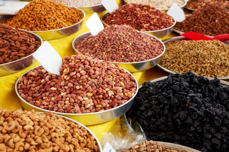 Various dried fruits in an authentic bazaar. Pile of roasted peanut, cashew nut, dry prune, maize, almond and nut in round metal trays in an authentic bazaar royalty free stock photos