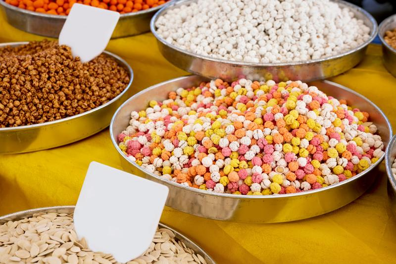 Various dried fruits in an authentic bazaar. Pile of sugar coated chickpea in round metal trays on an authentic bazaar counter stock photography