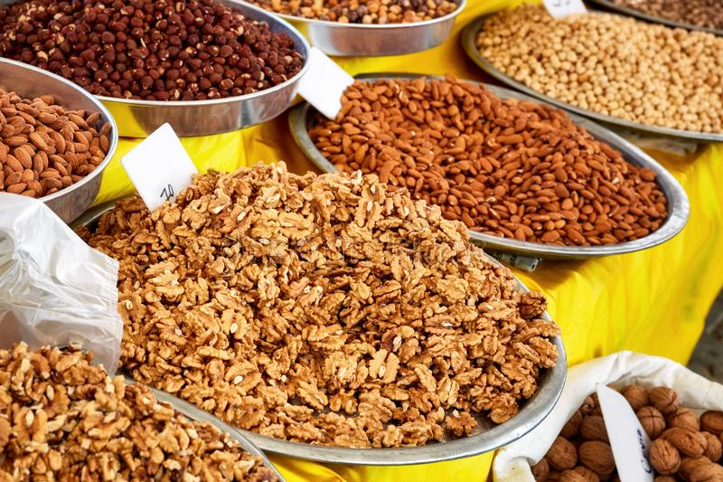 Various dried fruits in an authentic bazaar. Pile of walnut kernel, almond and nut in round metal trays in an authentic bazaar stock photos