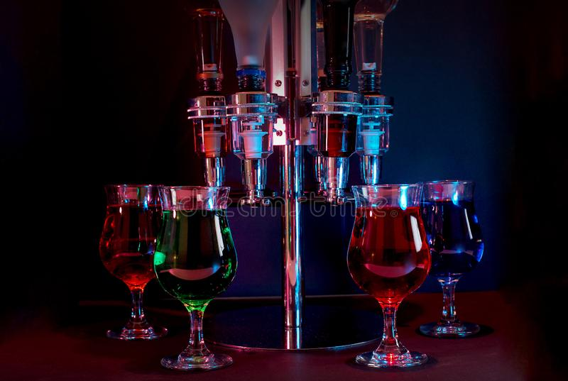 Various Drinks With Dispenser, Backlit In A Night Club. Various backlit alcoholic drinks with spindle dispenser, in a night club royalty free stock image