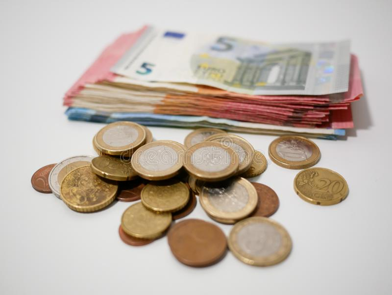 Various Euro coins and banknotes on a white desk. Notes and coins of various denominations. stock photos