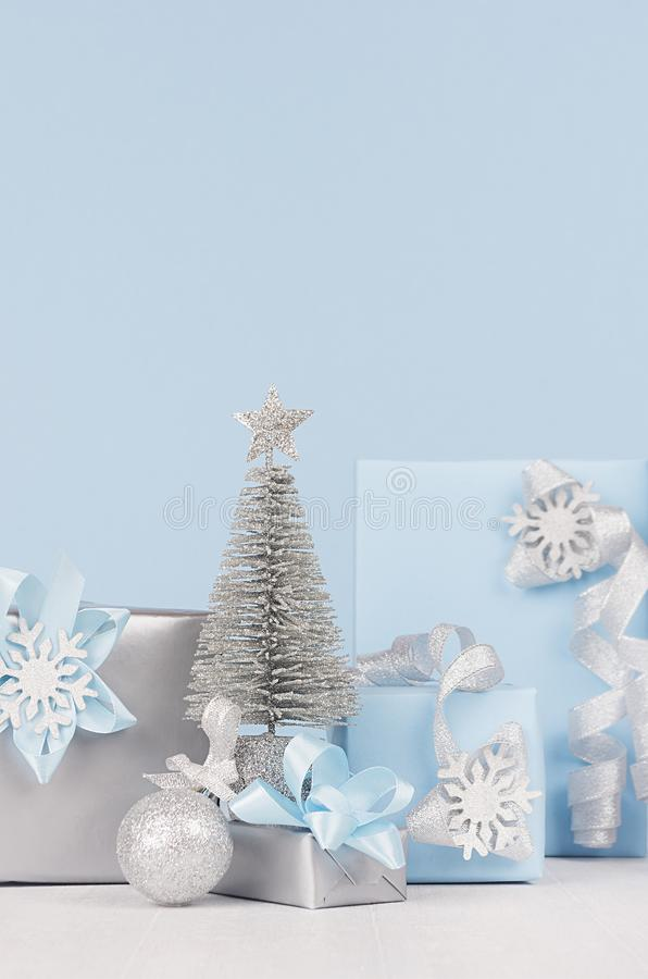 Various festive christmas gift boxes and decoration in soft light pastel blue color with shiny silver ribbons and silk bows. royalty free stock photography