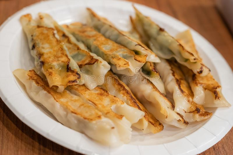 The various flavor of Pan-fried dumplings or gyoza in a paper plate placed. On a wooden table stock photography