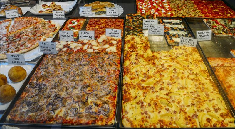 Various flavours of different pizzas, with Italian descriptions, for sale on a shop front window in Venice. Various flavours of different pizzas, with Italian royalty free stock images