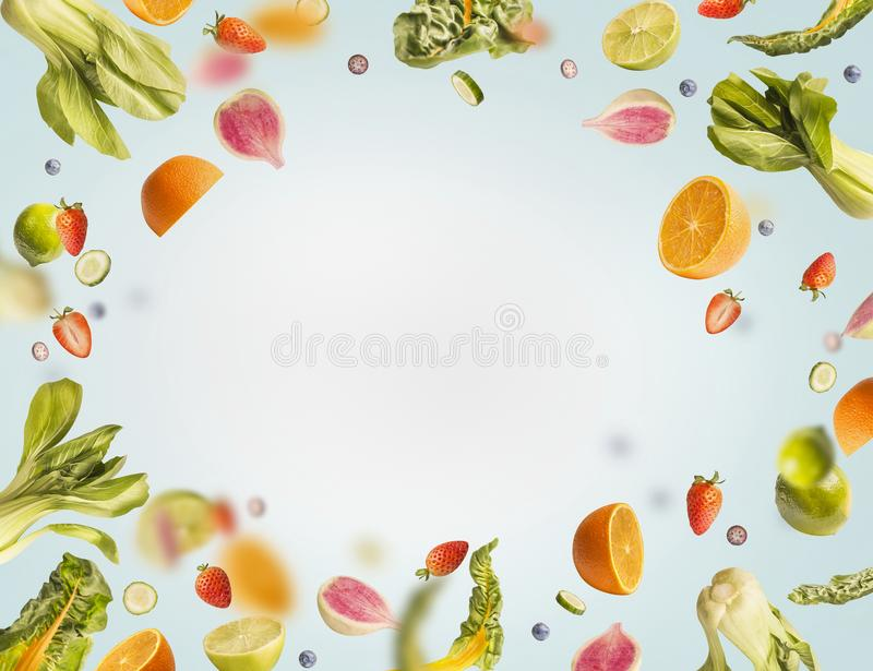 Various flying or falling summer fruits,berries and vegetables on light blue background, frame. Healthy detox food. Layout concept stock images